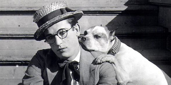 Harold Lloyd sitting on steps with dog